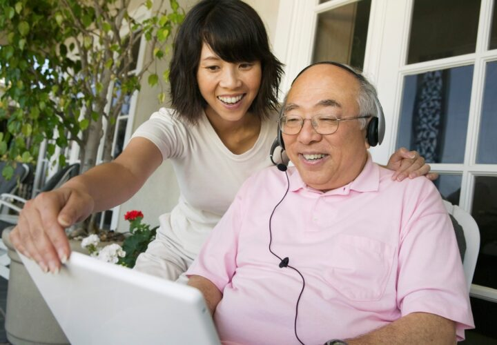 older man wearing headset to talk to ipad