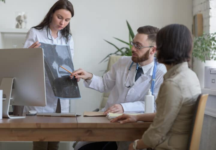 Doctor reviewing brain scans with colleagues