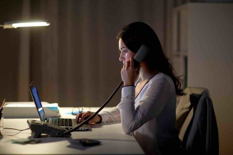 woman with laptop calling on phone at night office
