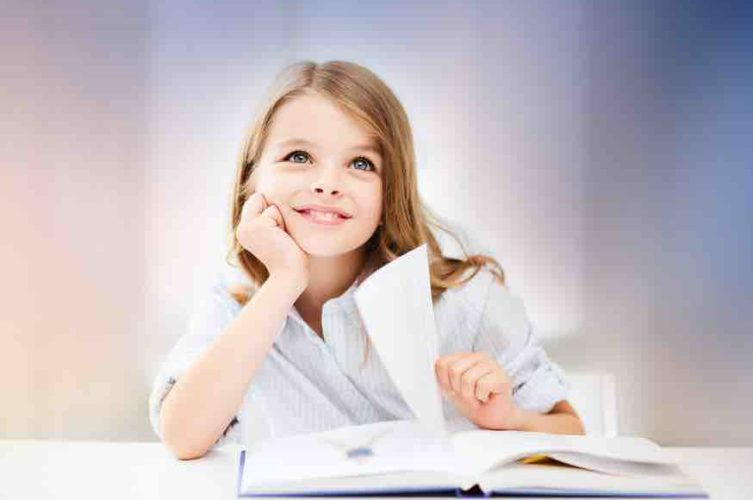 young girl sitting at desk in classroom