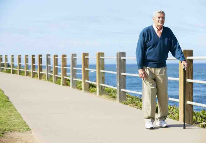 senior man walking with cane outdoors on walking path