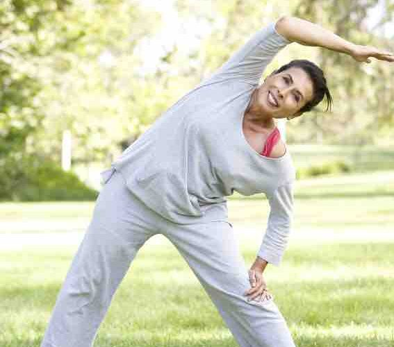 woman in her 60's exercising in a park