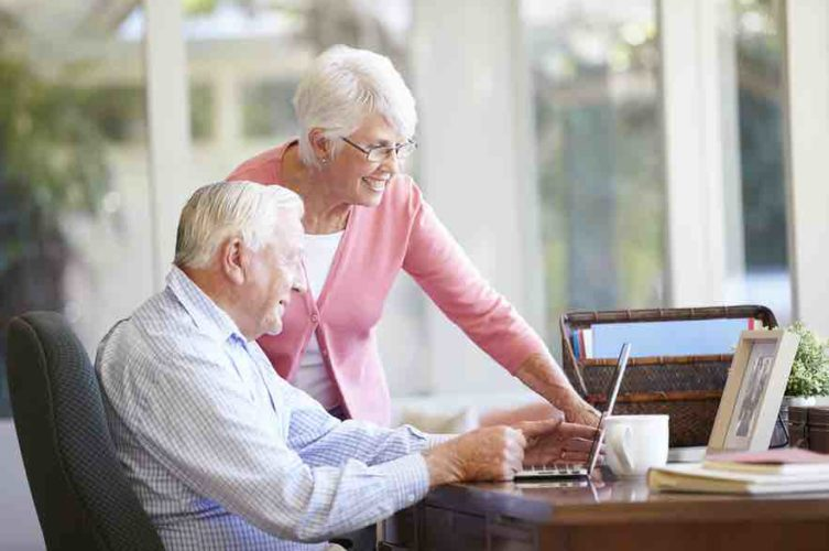 senior woman and man work on laptop computer at desk