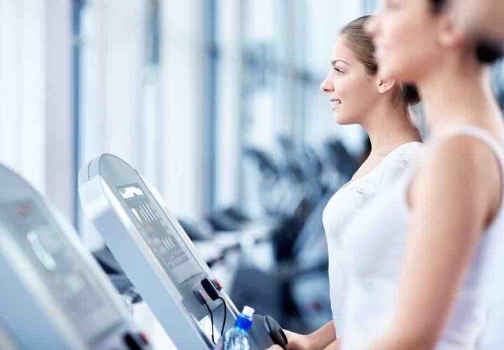 two women walking on treadmills